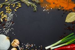 On a black background spices and vegetables. View from above. Stock Photo