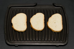 On a black background Three slices of bread Stock Image
