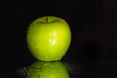 Black Background with a Wet Green Apple Stock Image