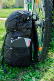 Black backpack with notebook, map and pencil outdoor near bike. Summer. Tourism concept. Royalty Free Stock Photo