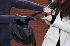 Black backpack stealing. A thief stealing a black leather backpack Royalty Free Stock Photos