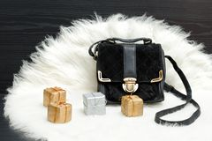 Black bag and gift box on white fur. Fashionable concept. Holida Royalty Free Stock Images