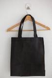 Black bag on hanger. Against white wall Stock Image