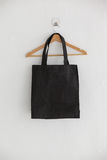 Black bag on hanger. Against white wall Royalty Free Stock Image