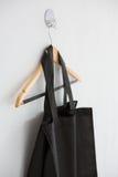 Black bag hanging on hanger. Close-up of black fabric bag hanging on hanger on white wall Royalty Free Stock Photos