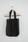 Black bag hanging on hanger. Black fabric bag hanging on hanger on white wall Stock Photo