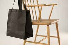 Black bag hanging on a wooden chair Royalty Free Stock Images