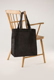 Black bag hanging on a wooden chair Royalty Free Stock Photos