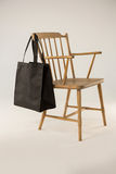 Black bag hanging on a wooden chair Stock Photography
