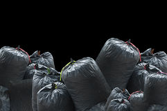 Black bag of rubbish isolated on black background Royalty Free Stock Images