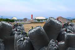 Black bag of rubbish isolated on industry landscape background Stock Photo