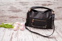 Black bag on a wooden background, pink tulips. Fashionable concept Stock Images