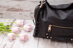 Black bag on a wooden background, pink tulips. Fashionable concept Stock Photography
