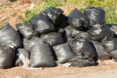 Black bags filled with garbage at roadside Stock Photo