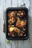 Hot and spicy glazed chicken legs baked with onions and garlic. In black baking tin there are hot and spicy glazed chicken legs baked with onions and garlic stock photo