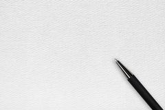 Black ball pen on the white paper background. White paper background with black ball pen and text space royalty free stock image