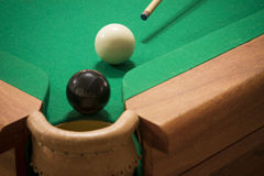 Black ball strike. Pool cue aiming the cue-ball before pocketing the black ball. Close up Stock Image