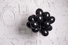 Black balloons against a white wall with frames
