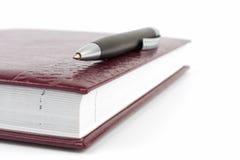 Black ballpoint pen lying on the cover book. Black ballpoint pen lying on the leather cover diary Stock Image