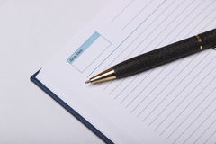 Black ballpoint pen lying on a notebook Stock Image