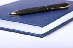 Black ballpoint pen lying on a notebook Royalty Free Stock Image
