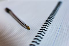 Black ballpoint pen lying in between the pages stock photo