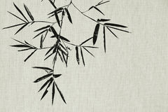 Black bamboo leaf and branch on fabric texture background Stock Photography