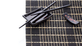Black bamboo mat with soy sauce and chopsticks over white Royalty Free Stock Photo