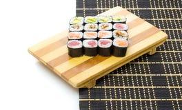 Black bamboo mat with sushi isolated on white background Royalty Free Stock Photos