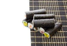 Black bamboo mat with sushi isolated on white background Royalty Free Stock Photo