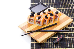 Black bamboo mat with sushi isolated on white background Royalty Free Stock Photos