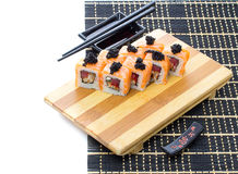 Black bamboo mat with sushi isolated on white background Royalty Free Stock Images