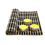 Black bamboo mat and three yellow candles Royalty Free Stock Photography