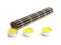Black bamboo mat and three yellow candles Stock Image