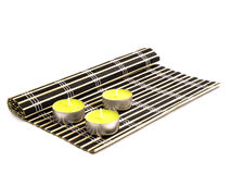 Black bamboo mat and three yellow candles Stock Photo