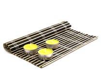 Black bamboo mat and three yellow candles Stock Photo