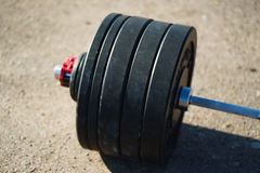 Black barbell isolated on asphalt background Royalty Free Stock Photos