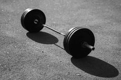 Black barbell isolated on asphalt background. Sun Royalty Free Stock Image