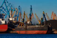 Black barge loading. In cargo port of Riga stock photography