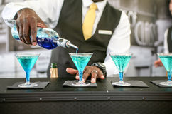 Black barman. Pouring blue colored cocktails Stock Image