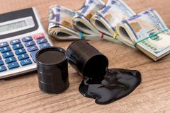 Black barrel with oil lies on dollar banknotes with calculator on desk. Sale of oil. Oil Stock Photos