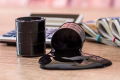 Black barrel with oil lies on dollar banknotes with calculator on desk. Sale of oil. Oil Stock Photo