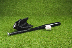 Black baseball bat with leather glove and ball on green grass Royalty Free Stock Image