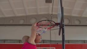 Black basketball player performing slam dunk