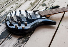 Black bass guitar on a wooden background Royalty Free Stock Photography