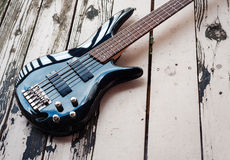 Black bass guitar on a wooden background Royalty Free Stock Image