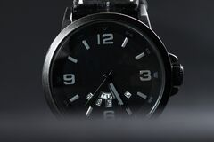 A black battery operated watch on black leather background