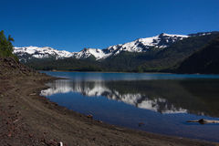 The black beach of the lake in Conguillio National Park in Chile. The black beach of the lake with the reflected mountains covered with snow in Conguillio Stock Photo