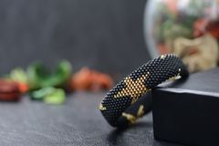 Black beaded bracelet with golden stars. On a dark background Stock Photos