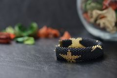 Black beaded bracelet with golden stars. On a dark background Royalty Free Stock Photo